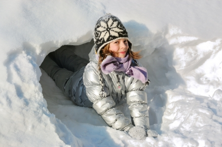 Happy child having fun with snow outdoors, winter vacation photo