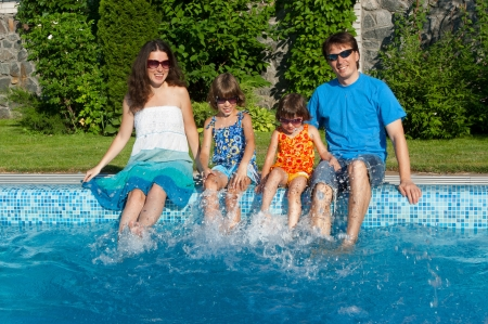 Family summer vacation  Happy parents with two kids having fun and splashing near swimming pool  Vacation with children Stock Photo