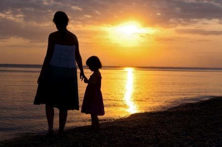Mother and kid silhouettes on sunset beach, family summer vacation photo