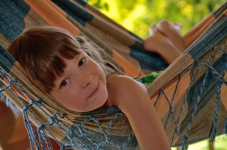 Little happy girl relaxing in hammock  Smiling kid on family summer vacation Reklamní fotografie