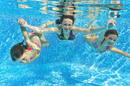 child swimsuit: Happy smiling family underwater in swimming pool. Mother and children swim and having fun. Kids sport on family summer vacation. Active healthy holiday