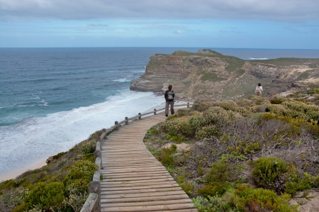 south coast: Tourist  on vacation walking on wooden path and looking at the beautiful view. Cliffs and ocean at Cape of Good Hope, South Africa Stock Photo