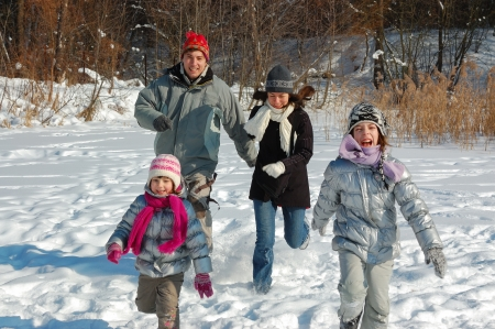winter woman: Happy family winter fun outdoors. Active smiling parents with kids playing with snow on winter vacation