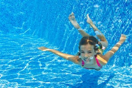 Glücklich lächelnde Unterwasser Kind im Schwimmbad, schöne, gesunde Mädchen schwimmt und Spaß im Wasser Kids Sport auf Sommerurlaub mit der Familie Aktivurlaub