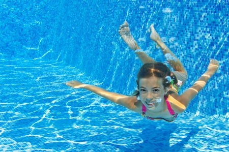 Happy smiling underwater child in swimming pool, beautiful healthy girl swims and having fun in water  Kids sport on family summer vacation  Active holiday Stock Photo