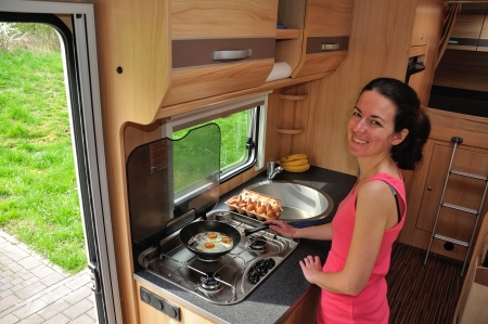 motorhome: Family vacation, RV holiday trip, camping  Happy smiling woman cooking in camper  Motorhome interior