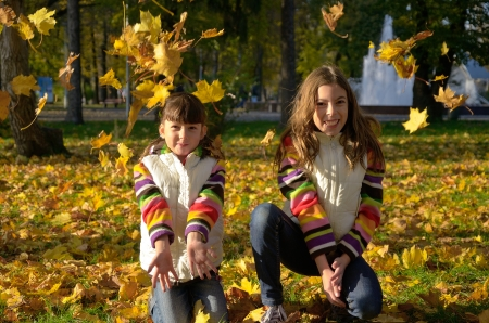 Happy children in autumn park, active kids having fun and playing with yellow leaves outdoors photo