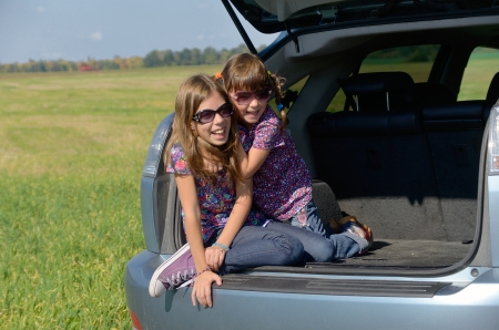 Family car trip on summer vacation, happy smiling kids travel, children having fun  Car insurance concept photo