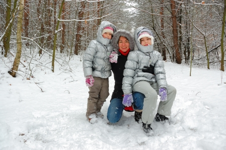 Family in winter forest, happy mother and kids having fun outdoors photo