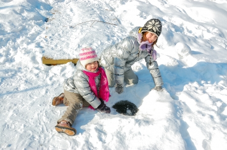 Kids having fun in winter outdoors, children playing with snow photo