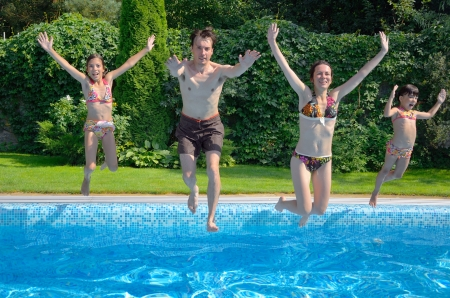 pool fun: Happy family with kids jumping to swimming pool, smiling parents and children having fun on summer vacation Stock Photo