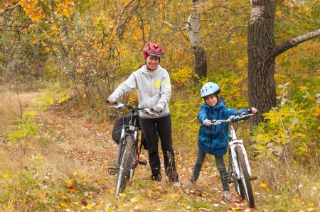 Happy family on bikes cycling outdoors, smiling active mother with kid on bicycles having fun, golden autumn in park  Family sport and healthy lifestyle photo
