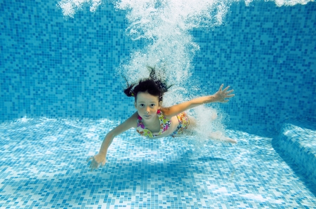 Happy smiling underwater child jumps to swimming pool, beautiful little girl swims and having fun  Kids sport on family summer vacation  Active healthy holiday photo