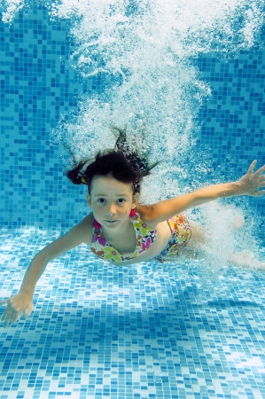 Usměvavé podvodní dítě skočí do bazénu, krásná holčička plavání a baví děti sportu na rodinnou letní dovolenou Aktivní zdravý dovolenou