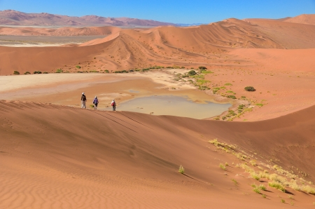 People walking on beautiful dune of Namib desert, traveling and hiking in South Africa photo