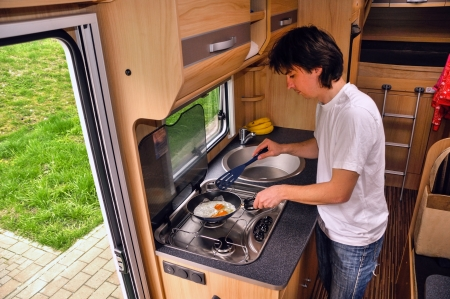 recreational vehicle: Family vacation, RV holiday trip, man cooking in camper  Motorhome interior