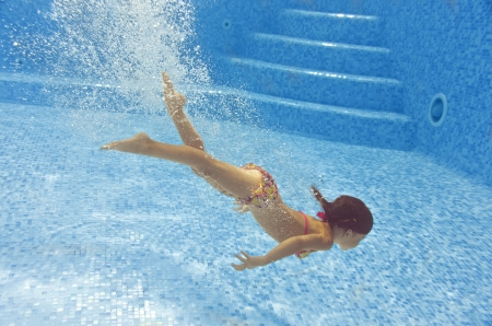 Happy child diving underwater in swimming pool, beautiful healthy girl swims and having fun in water. Kids sport on family summer vacation. Active holiday Stock Photo