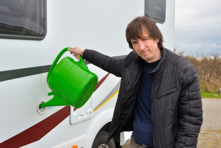 Man refilling camper  RV  water tank, traveling by motorhome photo