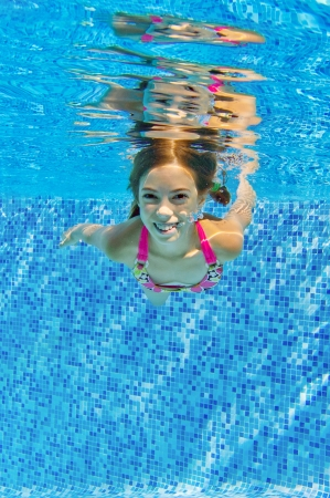 Happy active underwater child swims in pool, beautiful healthy girl swimming and having fun on family summer vacation, kids sport, vertical image