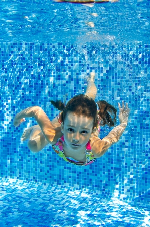 Happy active underwater child swims in pool, beautiful healthy girl swimming and having fun on family summer vacation, kids sport, vertical image photo