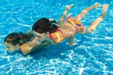 Happy active underwater children swim in pool, beautiful healthy girls swimming and having fun on family summer vacation, kids sport concept photo