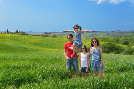 Happy family with children having fun outdoors on green field, spring vacation with kids in Tuscany, Italy Stock Photo - 19638453