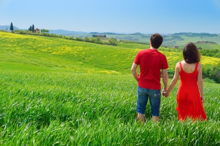 Romantic couple outdoors having fun and walking on green field, vacations in Tuscany, Italy photo