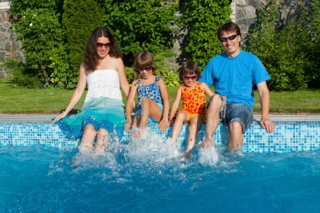 Happy parents with two kids having fun and splashing near swimming pool photo