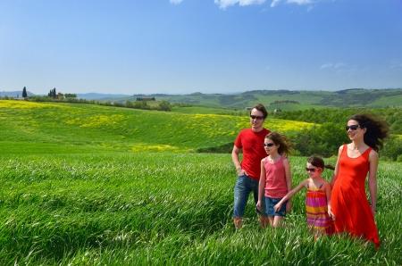 屋外グリーン フィールド、トスカーナ、イタリアでの子供との春の休暇を楽しんで子供たちと幸せな家族