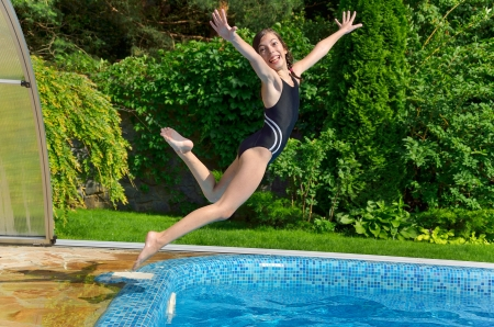 Happy girl jumps to swimming pool, active child having fun on vacation photo