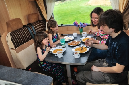 Family eating together in RV interior, travel in motorhome  camper, caravan  on vacation Stock Photo