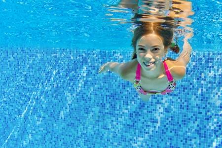 underwater: Happy active child swims underwater in pool Stock Photo