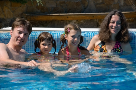 Happy family having fun in swimming pool on summer vacation, parents and kids photo