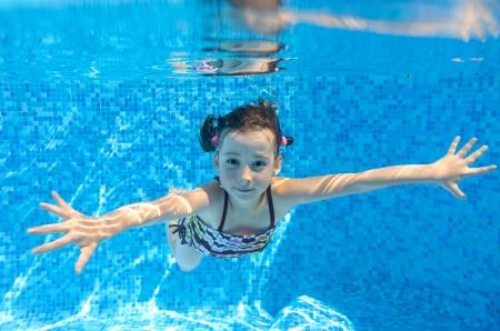 幸せのアクティブな子美しい健康な女の子水泳プールで水中泳ぐし、スポーツ コンセプトの子供家族の夏休みを楽しんで
