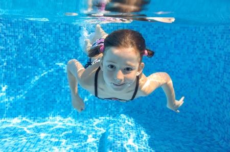 nadar: El ni?o feliz nadando activos bajo el agua en la piscina, hermosa ni?a saludable nadar y divertirse en vacaciones de verano de la familia, el deporte concepto ni?os