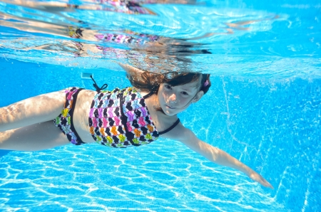 Happy active child swims freestyle in pool, underwater view, girl having fun on family summer vacation, kids sport concept photo