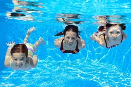 Happy family swim underwater in pool and having fun, mother and children on vacation Stock Photo