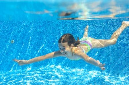 Šťastné aktivní dítě plave pod vodou v bazénu, krásná zdravá dívka plavání a baví se na rodinnou letní dovolenou, děti sportovní koncept