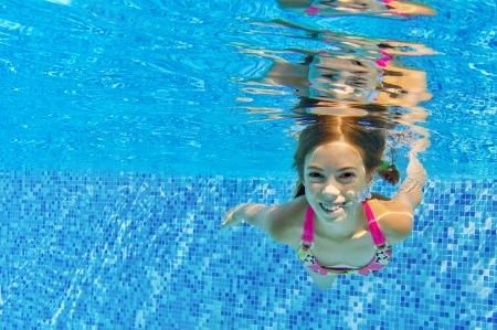 girl underwater: Gelukkig actieve kind zwemt onderwater in het zwembad, mooi gezond meisje zwemmen en plezier maken op familie zomervakantie, jonge sport concept