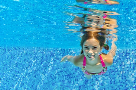 Happy active child swims underwater in pool, beautiful healthy girl swimming and having fun on family summer vacation, kids sport concept Banco de Imagens