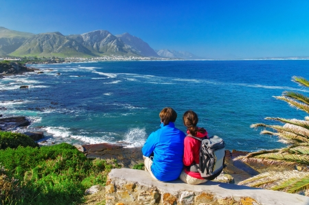 couple talking: Happy couple looking at beautiful ocean view in Hermanus, romantic vacation in South Africa