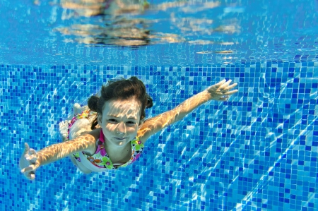 Happy active child swims underwater in pool, beautiful healthy girl swimming and having fun on family summer vacation, kids sport concept Stock Photo