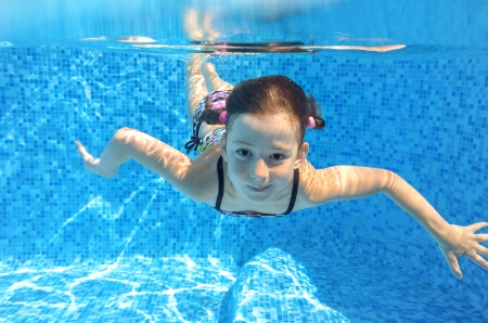 Happy active child swims underwater in pool, beautiful healthy girl swimming and having fun on family summer vacation, kids sport concept photo