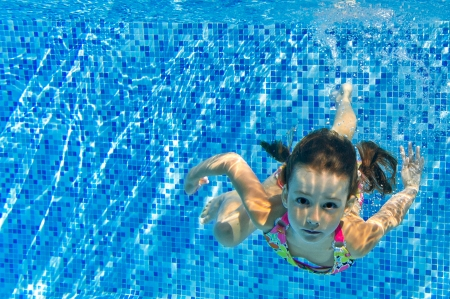 Happy active child swims underwater in pool, beautiful healthy girl swimming and having fun on family summer vacation, kids sport concept Standard-Bild