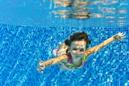 kids swimming: Happy active child swims underwater in pool, beautiful healthy girl swimming and having fun on family summer vacation, kids sport concept Stock Photo