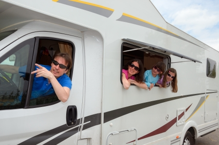Family travel in motorhome  RV  on vacation, happy parents and kids having fun near camper