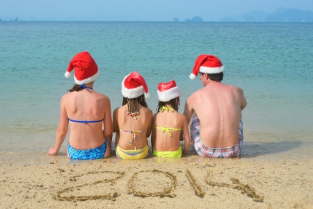 Family in santa hats having fun on beach, new year 2014 and christmas holiday concept photo