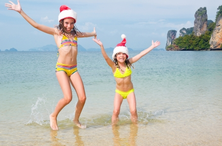 Children in santa hats having fun on beach, new year and christmas holiday concept photo