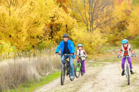 Happy family on bikes in autumn park, having fun, sport and cycling with kids photo
