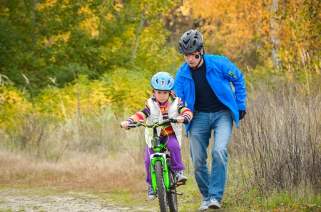 father teaching daughter: Father teaching child to ride bike in autumn park, family sport Stock Photo